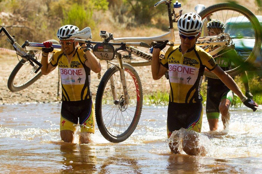 3. Etappe - Christoph Sauser und Burry Stander tragen die Bikes durch einen Fluss